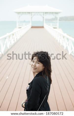 Asian women black jacket Smiling stood on a bridge made �¢??�¢??of wood. - stock photo