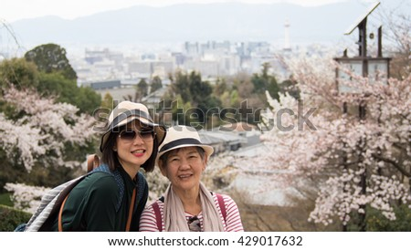 Asian women portrait - Senior mother and adult daughter looking and smiling to the camera. Background is Landscape Kyoto shooting from Kiyomizu-dera Temple, Kyoto, Japan - stock photo