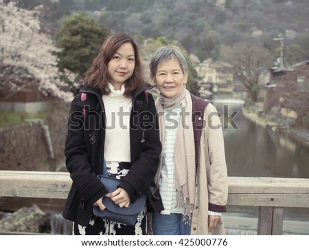Asian women portrait - Senior mother and adult daughter looking and smiling to the camera at Nishikyo-ku, Kyoto, Japan - stock photo