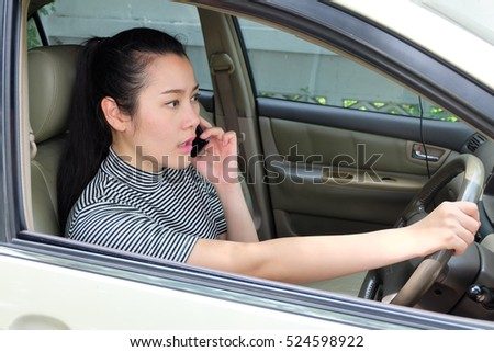 Asian women talking on a mobile phone while driving car.