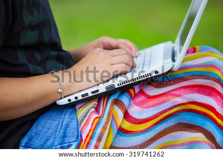 Asian women use labtop computer for search information in the garden.