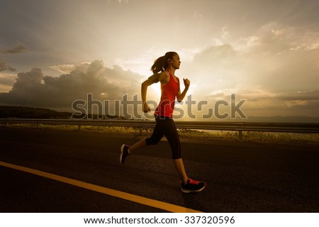 Asian women was jogging in the morning.and listens to music while running - stock photo