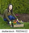 Asian women with box of mixed flowers in flowerbed with green bushes in background - stock photo