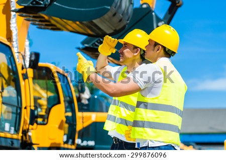Asian worker at construction machinery of construction site or mining company - stock photo