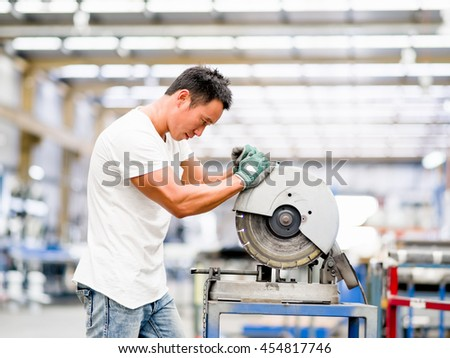 Asian worker in production plant on the factory floor - stock photo