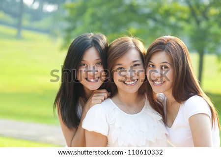 Asian young beautiful friends on vacation day, outdoor park - stock photo