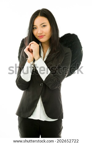 Asian young businesswoman dressed up as black angel handcuffs isolated on white background - stock photo