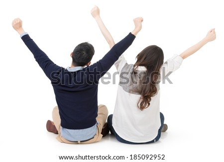 Asian young couple sitting on ground and stretching their hands feeling free, full length portrait on white background.