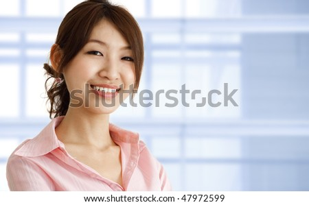 Asian young executive standing inside office building. - stock photo
