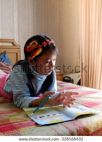 Asian young girl writing with a pencil in a notebook,Handwriting