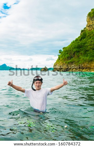 Asian young guy wearing diving mask with scuba approaching from the sea  - stock photo