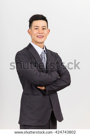 asian young handsome businessman standing arms crossed, smiling happy, looking at camera. - stock photo