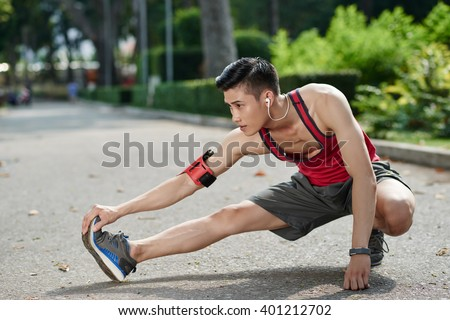 Asian young jogger stretching legs outdoors