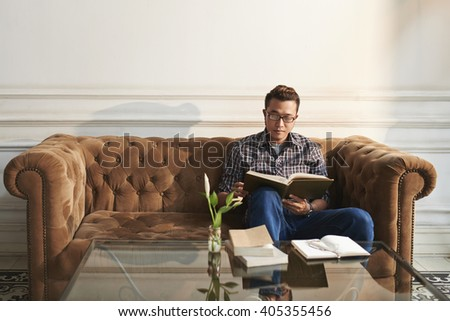 Asian young man sitting in large sofa with interesting book