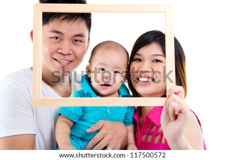 Asian young parent and baby boy looking fun through an empty frame - stock photo
