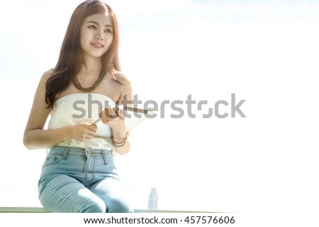 Asian young smile business or student working with tablet,  blurry and soft focus, has fair lighting, background has white sky, portrait woman - stock photo