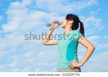 Asian young woman drinking water after training - stock photo