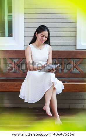Asian young woman using digital tablet outside on home summer. Active lifestyle happy young adult on relaxing day at home. - stock photo