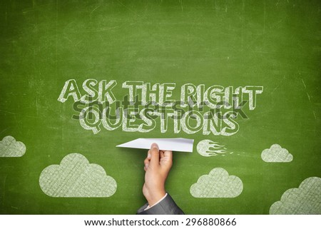 Ask the right questions concept on green blackboard with businessman hand holding paper plane - stock photo