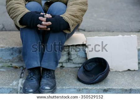 Asking for help. Depressed old beggar is sitting outside and waiting to get some help. - stock photo