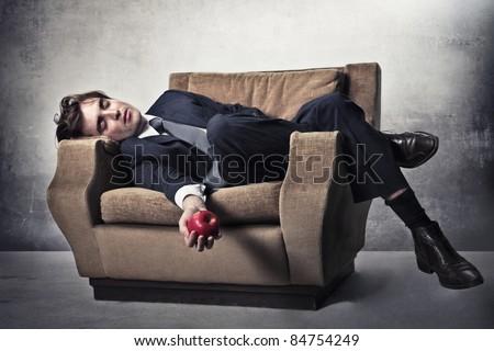 Asleep businessman lying on an armchair with an apple in his hand - stock photo