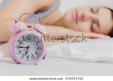 Asleep caucasian young woman with alarm clock in focus. - stock photo