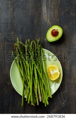 Asparagus and avocado on dark wooden background. Vegetarian food, health or cooking concept. Top view. - stock photo
