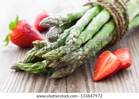 asparagus and strawberries on wood - stock photo