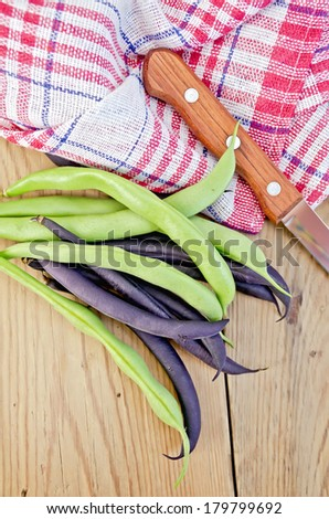 Asparagus beans green and purple, napkin, knife on background wooden plank - stock photo