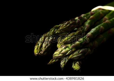 Asparagus black background / A bunch of fresh organic asparagus on a black background - stock photo