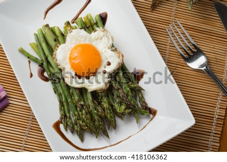 Asparagus cooked with eggs served on a plate on the table
