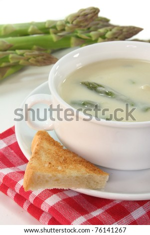 Asparagus cream soup with fresh asparagus and a slice of toast - stock photo