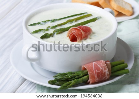 Asparagus cream soup with ham closeup in white bowl and croutons. horizontal   - stock photo