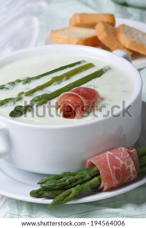 Asparagus cream soup with ham closeup in white bowl and croutons. vertical   - stock photo