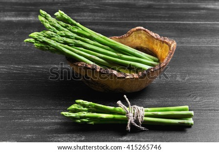 Asparagus green on a dark black background wooden surface, asparagus beam tied with rope and twine in a wooden bowl especially for asparagus, handmade from olive wood - stock photo