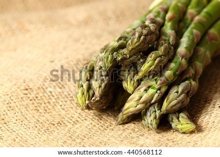 Asparagus hessian / A bunch of fresh organic asparagus on a hessian background - stock photo