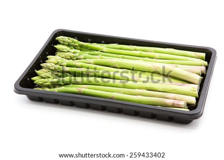 asparagus in black plastic tray on a white background,Selective focus. - stock photo