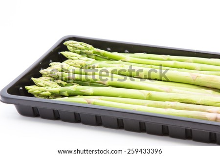 asparagus in black plastic tray on a white background,Selective focus and close up. - stock photo