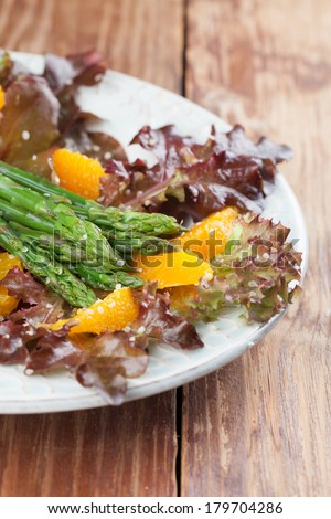 Asparagus salad with oranges, lollo rosso lettuce and hemp seeds - stock photo