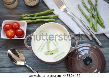 Asparagus soup on wooden table - stock photo
