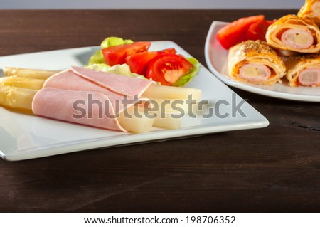 asparagus with ham and tomato on lettuce leaf - stock photo