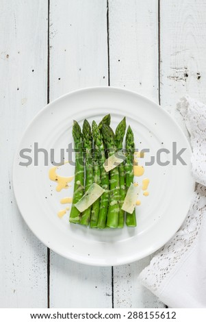 Asparagus with hollandaise sauce and parmesan captured from above. White planked wooden table as background. Background layout with free text space. - stock photo