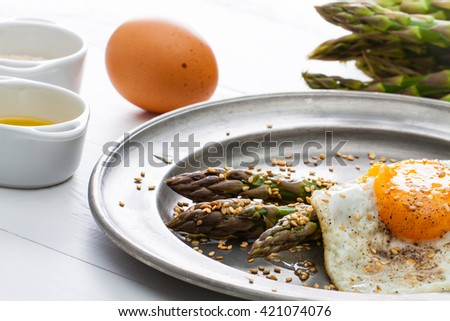 Asparagus with roasted sesame and fried egg on rustic iron plate.
