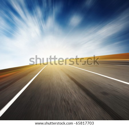Asphalt blurred road and sunlight and blue sky with blurred clouds - stock photo