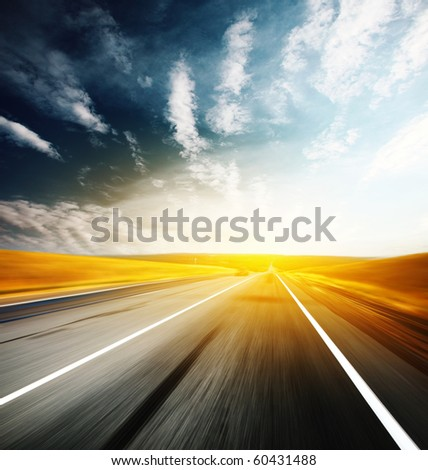 Asphalt blurry road and sky with clouds - stock photo