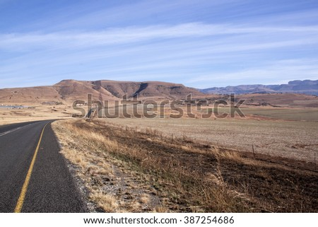 asphalt country road stretching through a dry winter landscape in Drakensberg South Africa - stock photo