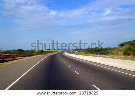 asphalt highway through a rural landscape - stock photo