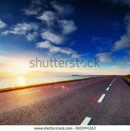 Asphalt road along the sea at sunset. - stock photo