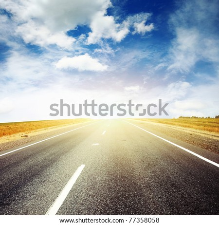 Asphalt road and bright blue sky with clouds - stock photo