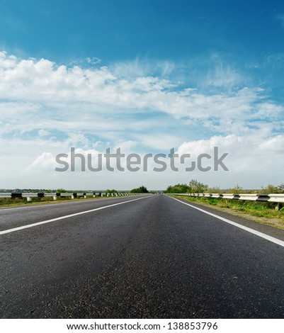 asphalt road and cloudy sky - stock photo